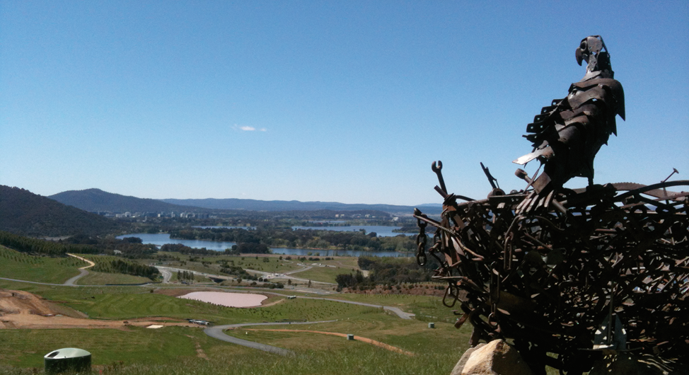 In the foreground is a metal sculpture of an eagle standing on a nest. In the background is the arboretum and the city of Canberra.