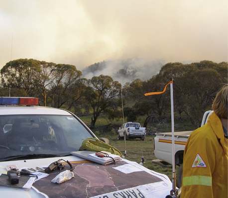 An emergency services vehicle in the foreground with equipment and maps on the bonnet. In the background is smoke from a controlled fire on a hillside.