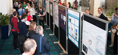 A crowd of people are looking at stands displaying information posters in a long wide hallway.