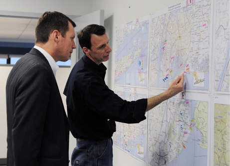 Timothy Manning and another man examine several maps on the wall, on which different sites are marked.