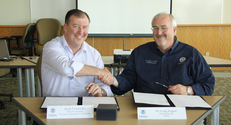 Mark Crosweller, Director General, Emergency Management Australia shakes hands with the United States Federal Emergency Management Agency's Administrator, Craig Fugate as they sign an agreement.