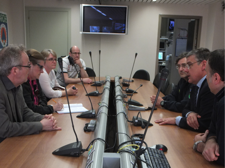 A group of people sitting around a teleconference table, having a discussion.