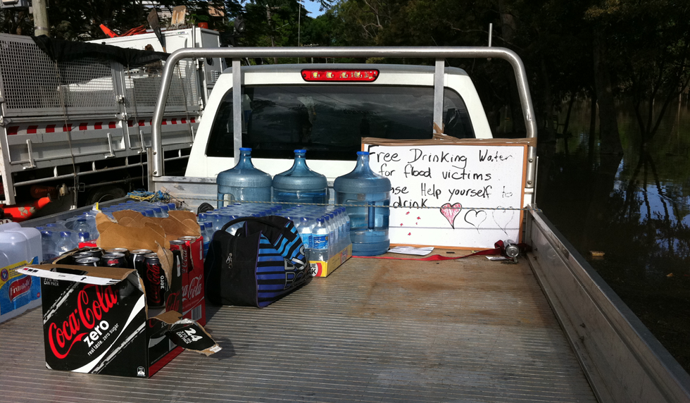 The tray of a ute is half-full of different types of beverages, including soft drink and bottled water. A sign says 'Free drinking water for flood victims, please help yourself to a drink'.