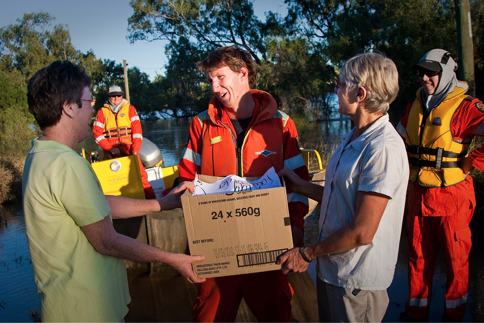 Five people are shown by the bank of a flooded river. Two of the people are receiving a food parcel from an emergency services volunteer, while another two emergency services personnel stand on in the background.