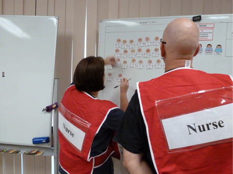 Two nurses use a whiteboard for complex incident response planning.