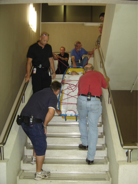 A Nursing team practicing carrying a fixed stretcher down a flight of stairs.
