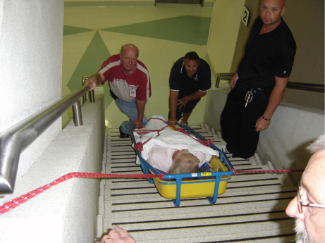 A stretcher is secured with ropes as a nursing team manoeuvre it down the stairs.