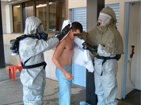 Two people wearing breathing apparatus and biohazard suits practice decontaminating a practice subject.