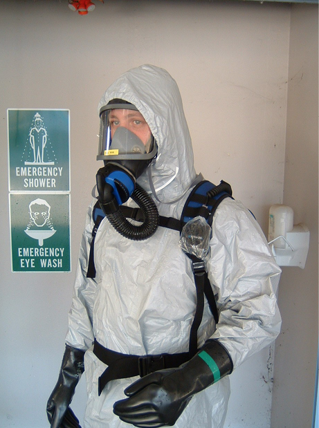 A person wearing breathing apparatus and a biohazard suit, standing under an emergency shower.