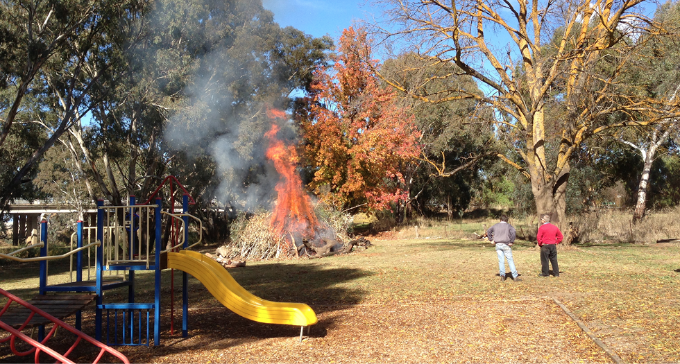 A photo of a park in Carisbrook, with play equipment in the foreground. In the background, residents tend a bonfire.