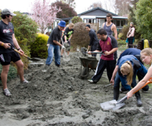 A photo of students helping with recovery efforts by shovelling mud in the front yard of a home.
