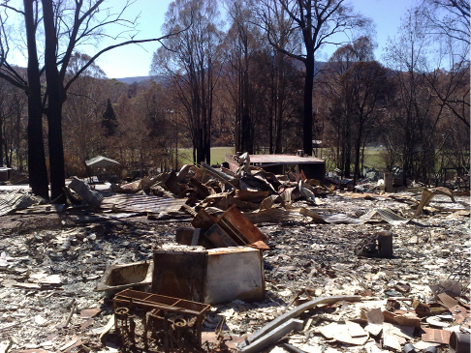 A photo of burnt bushland and a property. There are piles of burnt rubble piled around the property, and the skeletons of some buildings.
