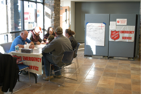 A photo of five Salvation Army volunteers having a discussion at a table.