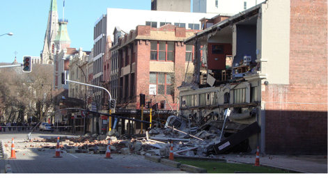 A photo of a street in Christchurch after an earthquake. It shows damaged buildings and street fixtures, and rubble that has fallen onto the footpath and road.