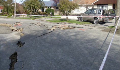 A photo of a damaged street in a residential neighbourhood. The street is broken up and large holes are visible. The area is marked off with tape to prevent people from driving and walking over it.