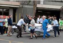 A photo of the front of the Christchurch Hospital Emergency Department. Several people are standing or walking in front, and hospital personnel are moving a patient on a stretcher.