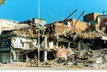 A photo the damaged Newcastle Workers Club. The building is essentially demolished, with parts of the building's framework exposed and huge piles of rubble around it.