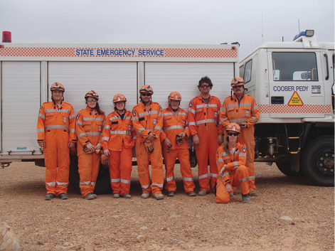 A photo of the volunteers (8 in total) standing in front of an SES building, and beside an SES emergency truck. The volunteers are wearing their orange SES uniforms.