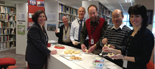 A photo of six people standing at a library counter eating scones.