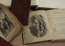 A photo of some old books. The pages are yellowed and the edges torn. They appear to be leather bound.