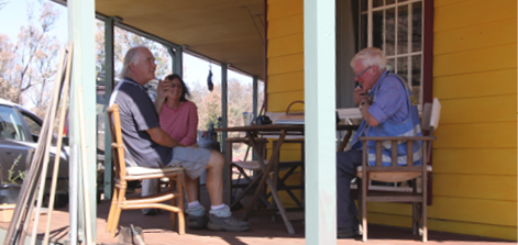 A photo of a male researcher interviewing a man and a woman. They are all sitting outside on the porch of a weatherboard building.