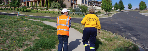 A photo of a female researcher and a female member of the NSW Rural Fire Service walking up a suburban street, with their backs towards us.