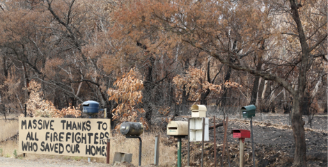 A photo of a hand-painted thank-you sign in front of a group of roadside mailboxes, which reads 'Massive thanks to all the firefighters who saved our home'. In the background the bush is burnt.