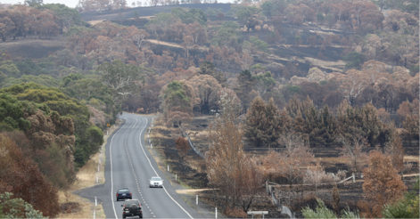 A photo of a highway running through rural properties among burnt bushland.