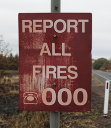 A photo of a partly fire-damaged emergency services sign, which reads 'report all fires, 000'.