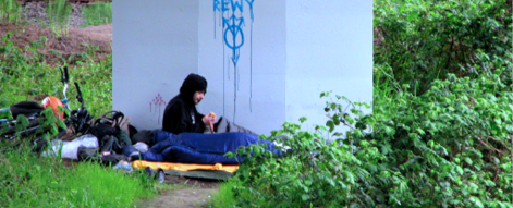 A person outside sitting among trees and vegetation, against a concrete structure. There are some belongings around him, such as a sleeping bag, a bike and some bags.