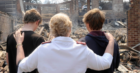A photo of a female relief worker with her hands on the shoulders of two male teenagers, with their backs towards us. They are standing in front of a home that has been reduced to rubble.
