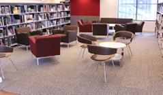 A photo of a sitting area, with small tables and some chairs among the bookshelves.