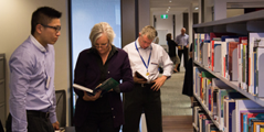 A photo of three people in a library, browsing the books.