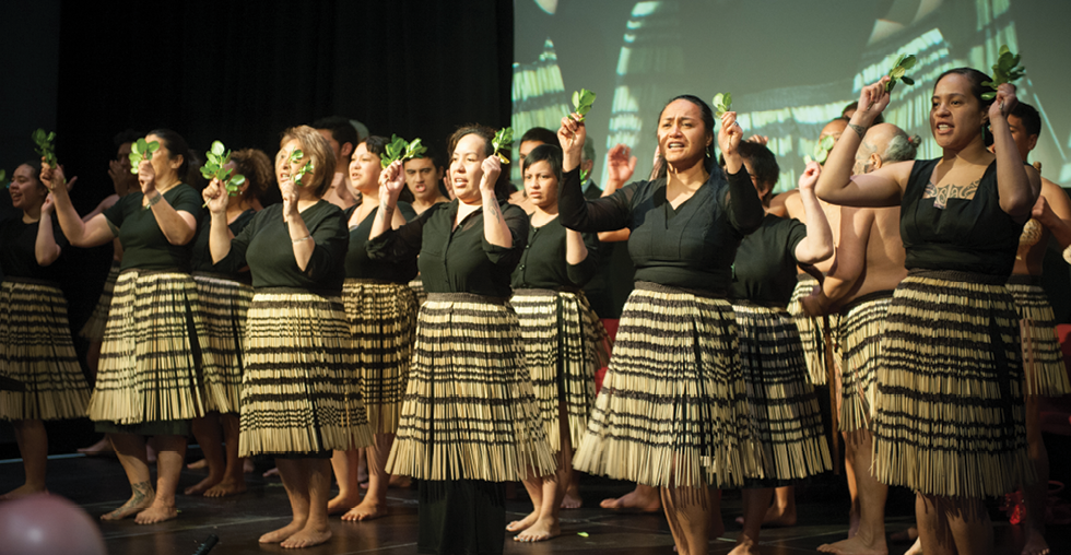 Maori men and women wearing grass skirts performing a traditional dance.