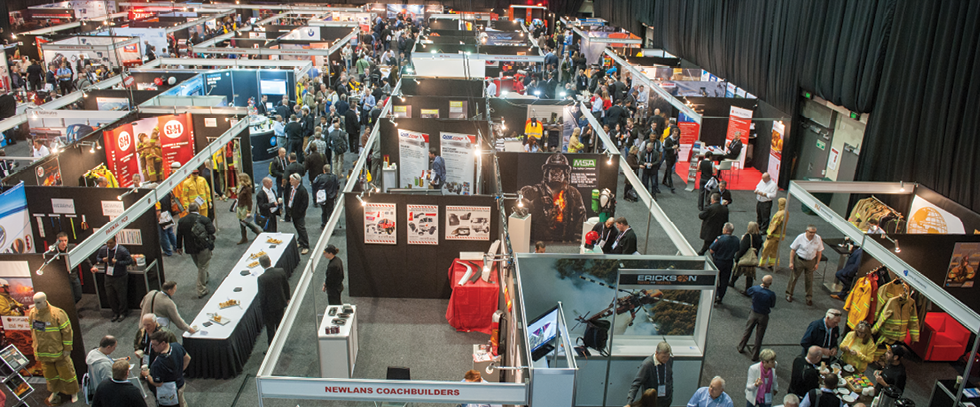 An overhead photo of a trade show, with many booths and people walking around.