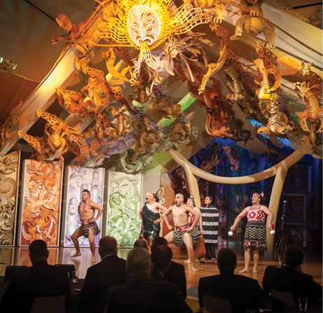 Maori men and women performing a traditional ceremony under an elaborately decorated roof