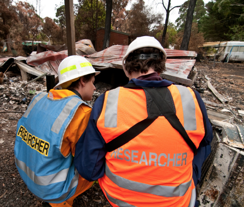 Two people wearing a high visibility 'Researcher' vests, are inspecting the remains of a burnt building.