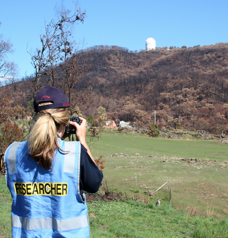 A woman wearing a blue safety vest with 'Researcher' across the back is taking a photo of an observatory on a distant hill.
