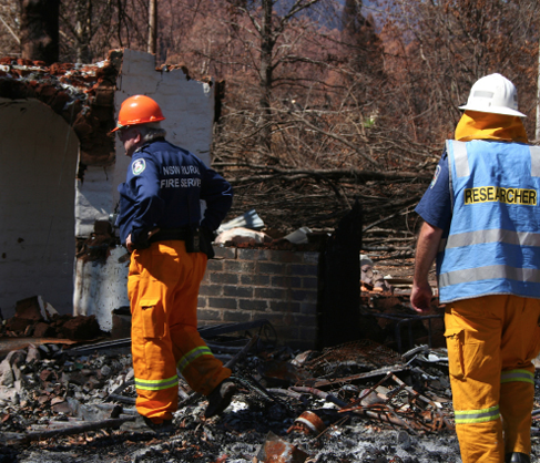 Two members of the NSW Rural Fire Service, one wearing a blue 'Researcher' vest, are inspecting the remains of a burnt building.