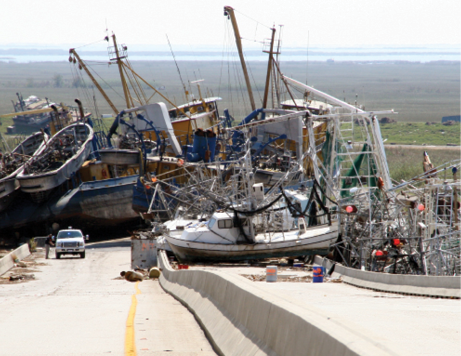 The downward slope of a concrete dual-carriageway road bridge is completely blocked by the wreckage of several commercial fishing boats. Flat green land stretches some distance beyond the boats to the shoreline in the background.