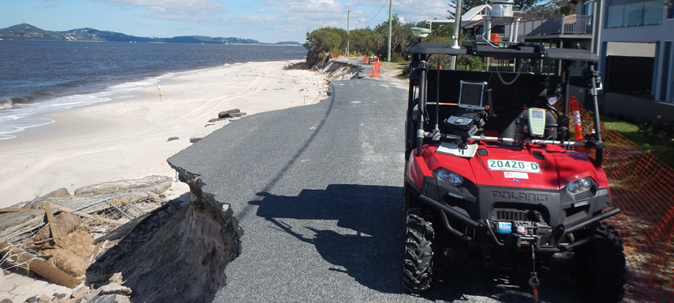 A bitumen road alongside a beach has been eroded. An off-road buggy is parked on the road in front of some houses.