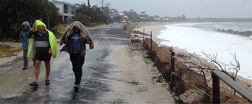 Three adults wearing rain jackets are walking on a bitumen road bordered by a beach and houses. Large waves are washing right up the beach eroding the road and there is sand on the road.