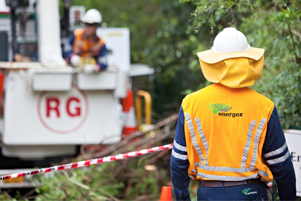 A man wearing Energex workwear, safety vest and hard hat is watching another Energex worker operating some kind of heavy machinery in the background. There are fallen branches in the middleground.