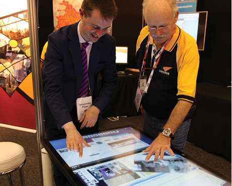 A young man wearing a suit and an older man wearing a polo shirt are interacting with a digital display table.