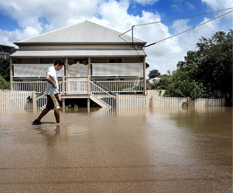 A man wearing shorts and t-shirt is wading ankle-deep through brown water past an elevated timber house whose support posts and picket fence are partially submerged. The sky is blue with white clouds.