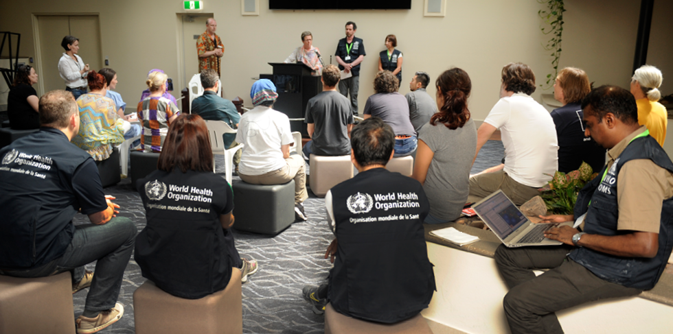 A group of adults seated on ottomans in a large room are being addressed by four other adults. Several people in the room are wearing World Health Organization vests.