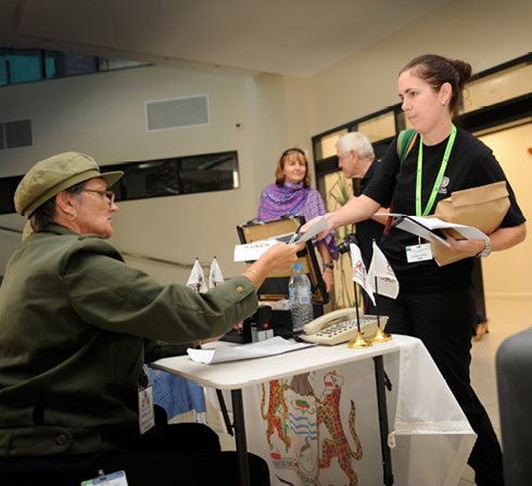 A young woman wearing a lanyard is exchanging papers with an older woman seated at a registration table in a foyer. An older man and woman are conversing in the background.