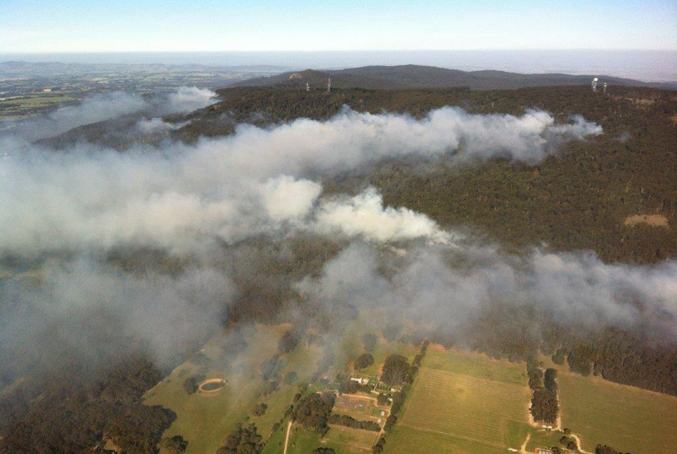 An aerial view of a rural landscape with forested hills surrounded by fields. Isolated spot fires are burning in the forest with the smoke streaming low across the landscape.