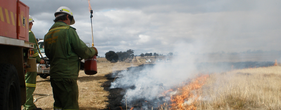 Two men wearing coveralls and hard hats are standing next to a fire truck stopped in open, dry grassland. One man is holding a fuel cylinder with burner. An arc of low fire is moving across the grass away from the men.