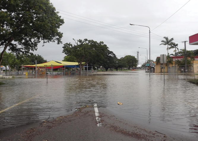 A road that runs through a country town is flooded. On one side of the flooded road are buildings, on the other side is a park and playground, all surrounded by floodwater.
